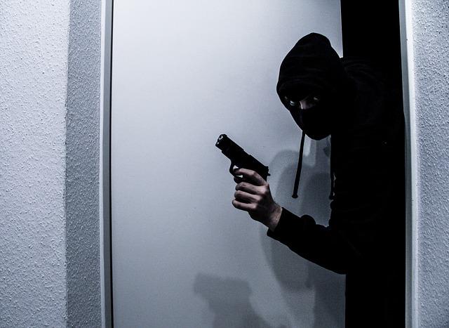 zloděj s pistolí v ruce